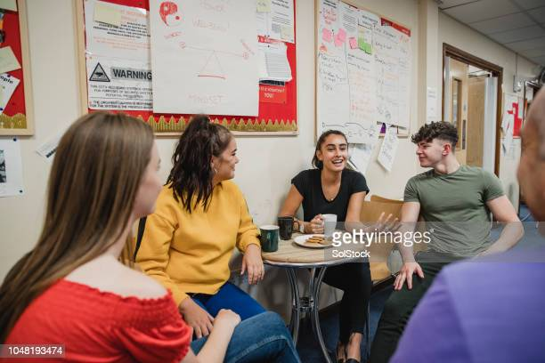 teenagers relaxing with tea at youth club - social issues stock pictures, royalty-free photos & images