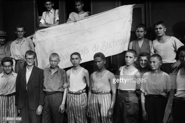 Teenagers repatriated from the German concentration camp of Buchenwald pose in front of a banner hung on the train that brought them back from...