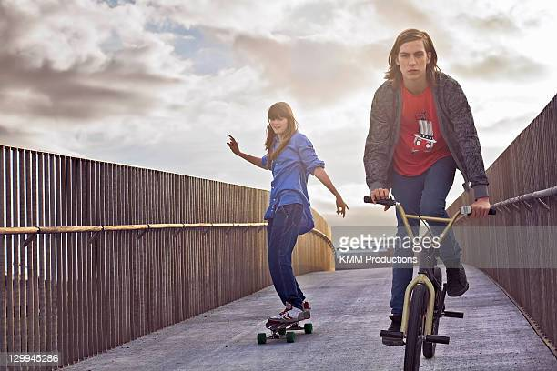 Teenagers riding bicycle and skateboard