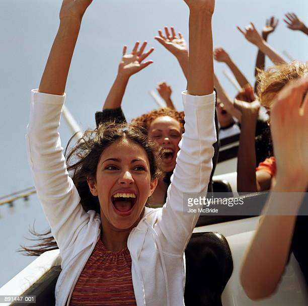 teenagers (14-17) riding   rollercoaster, hands raised in air - 遊園地の乗り物 ストックフォトと画像