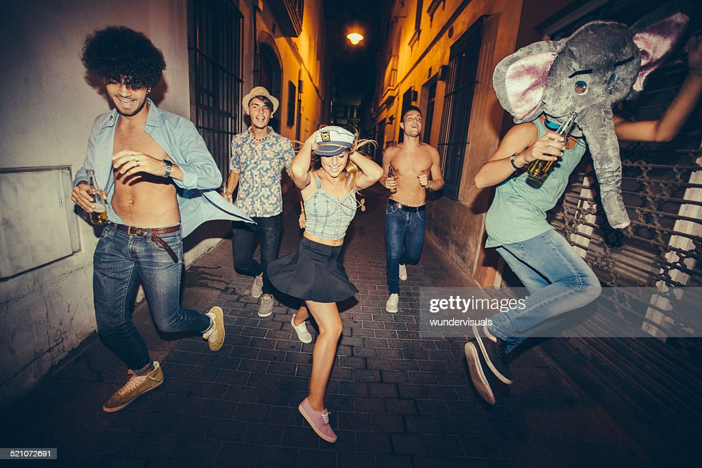 Teenagers Running Down Street During Night Party : Stock Photo