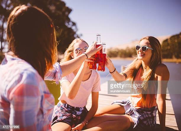 Teenager sagen cheers mit alcopops im Freien an einem sonnigen Tag