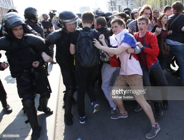 Teenagers shouting antiPutin slogans push policemen during the demonstration against President Vladimir Putin at Pushkin Square in Moscow Russia...
