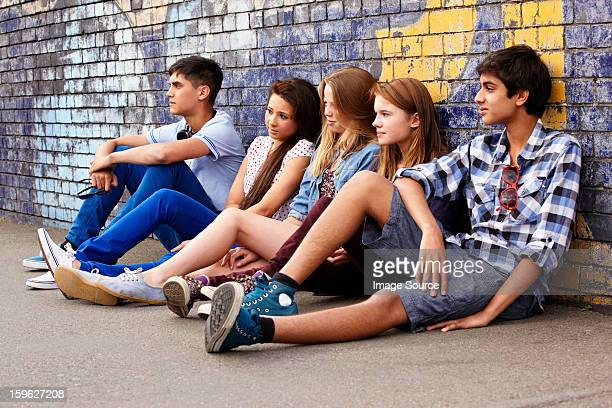 Teenagers sitting against a wall