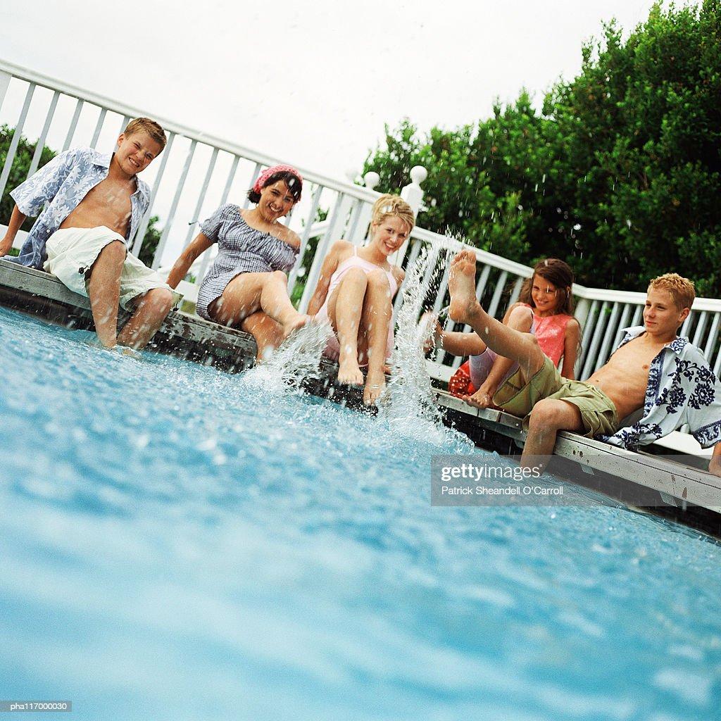 Teenagers sitting around swimming pool, splashing : Stockfoto