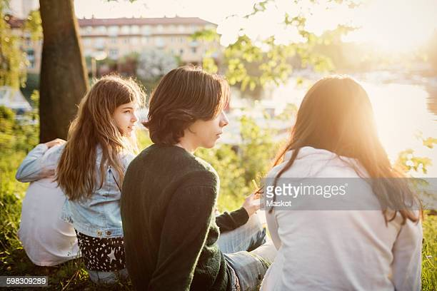 teenagers sitting at lakeshore on sunny day - solo adolescenti foto e immagini stock