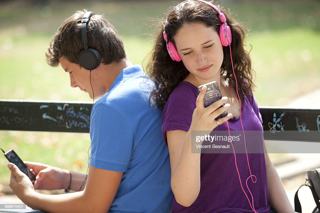 Teenagers sitting back to back on a bench : Stock Photo
