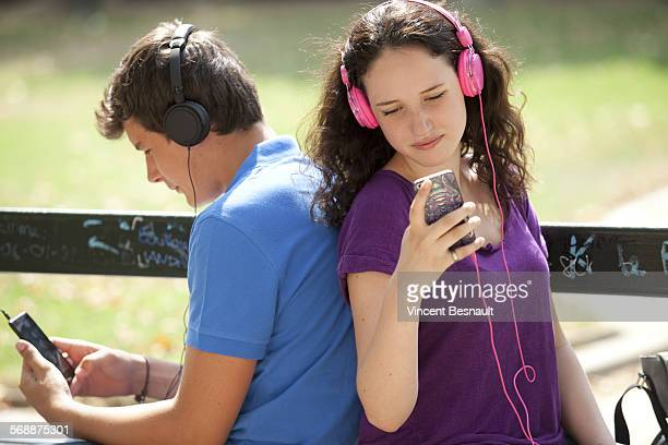 Teenagers sitting back to back on a bench