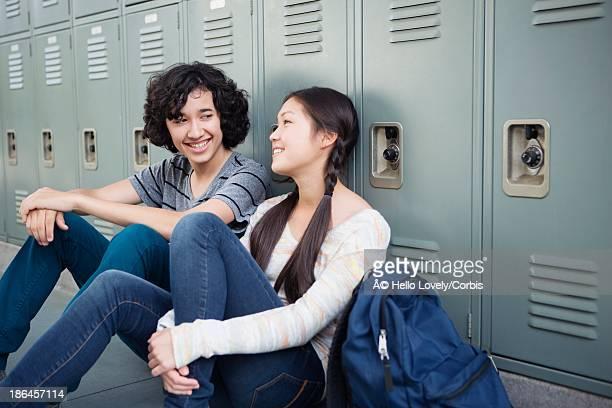 Teenagers (13-15) sitting in school corridor talking