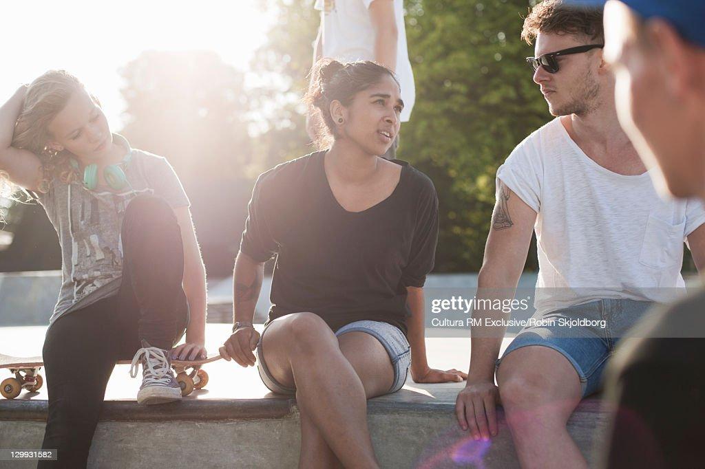 Teenagers sitting on ramp at skate park : Photo