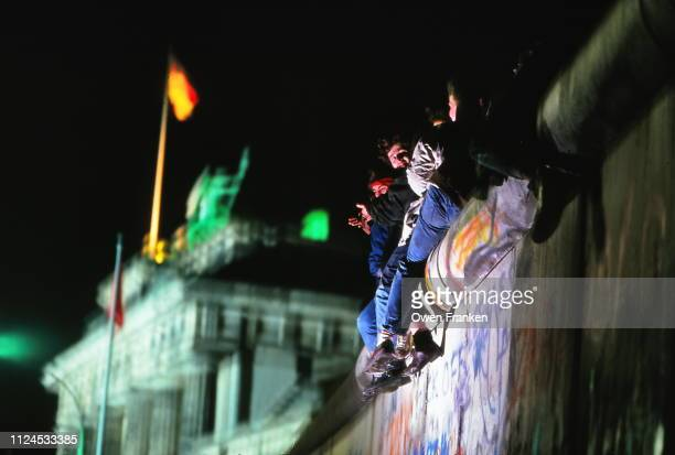 teenagers sitting on the berlin wall, near the brandenburg gate, after the opening of the wall in november 1989 - berlin wall stock pictures, royalty-free photos & images