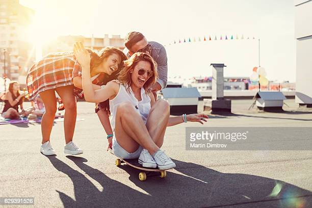 Teenagers skateboarding on rooftop terrace