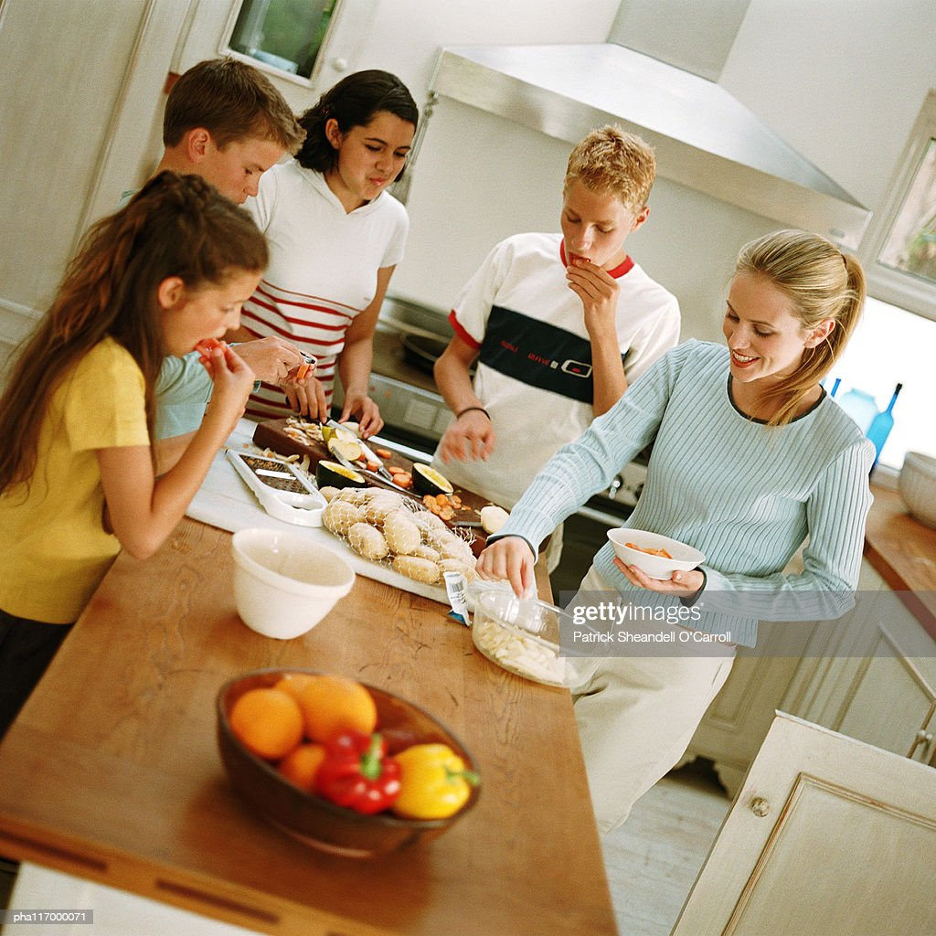 Teenagers snacking around table in kitchen : Stockfoto