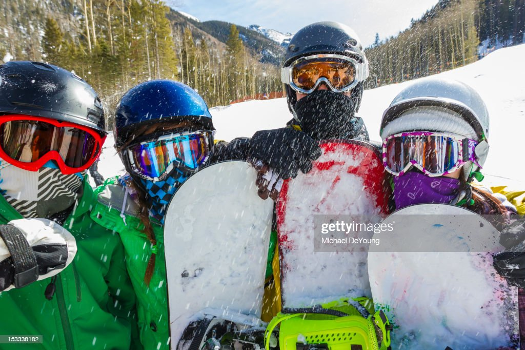 Teenagers snowboarding together