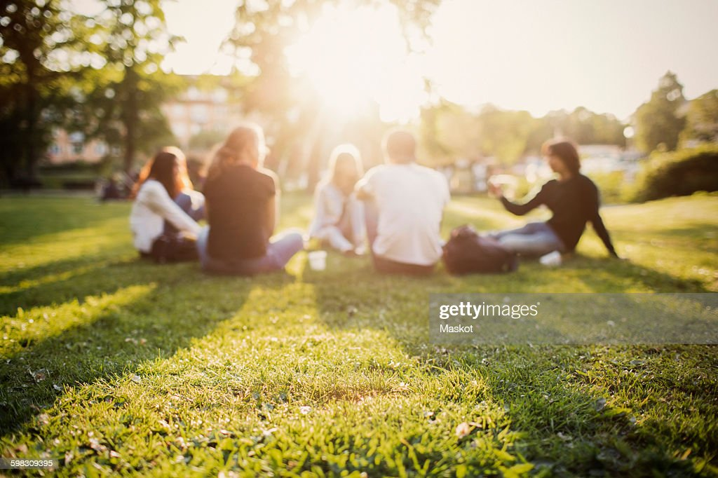 Teenagers spending leisure time while sitting at park : Foto de stock