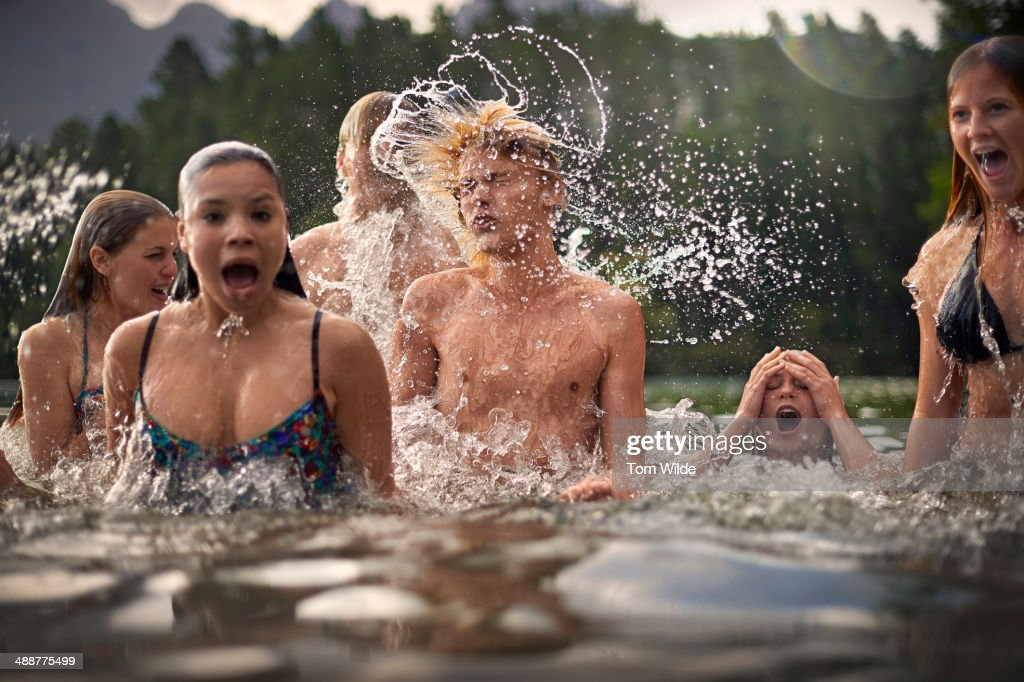 A group of teenage friends splashing and fooling around in the water