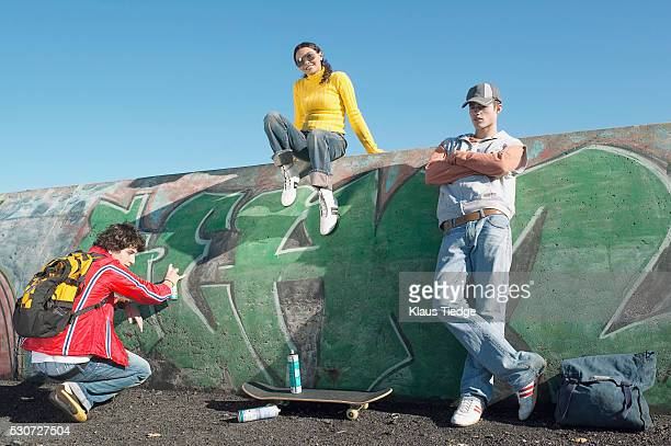 Teenagers spray painting a concrete barrier and hanging out