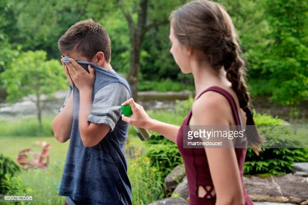 Teenagers spraying insect repellant on each other in summer nature.