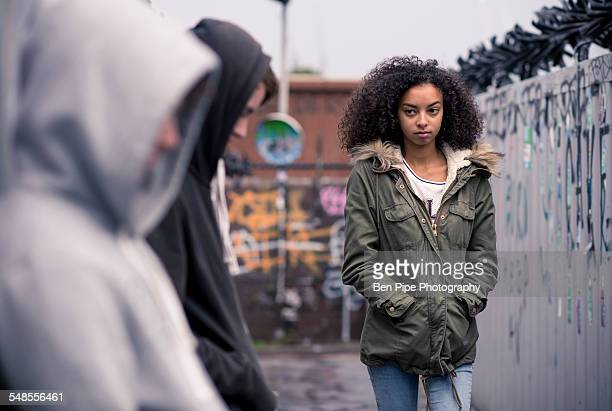 Teenagers standing against wall with graffiti