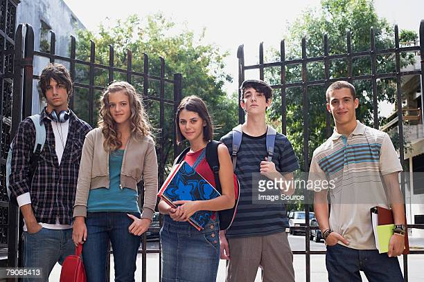 Teenagers standing near metal gates