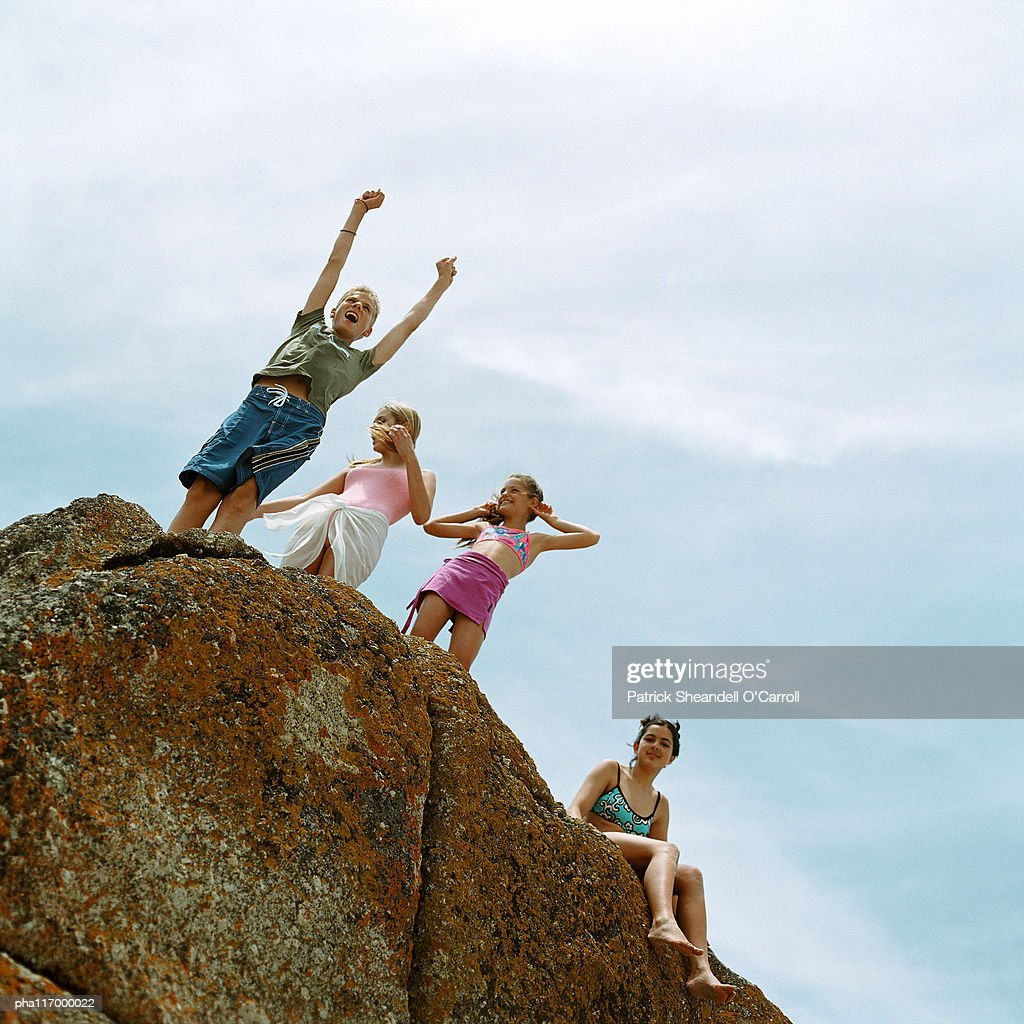 Teenagers standing on rock, low angle view : Stockfoto