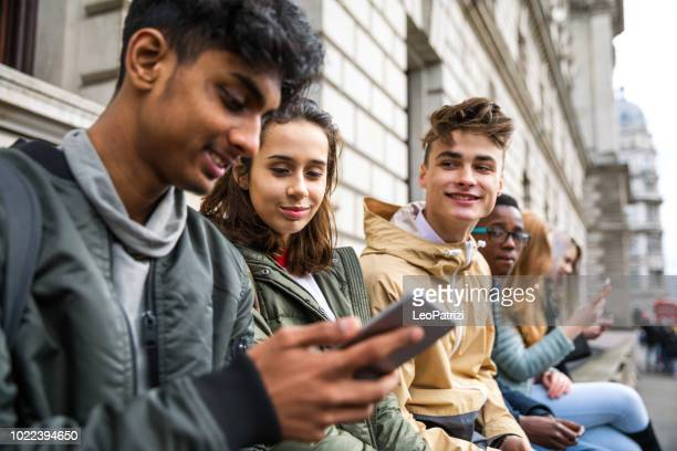 teenagers students using smartphone on a school break - generation z stock pictures, royalty-free photos & images