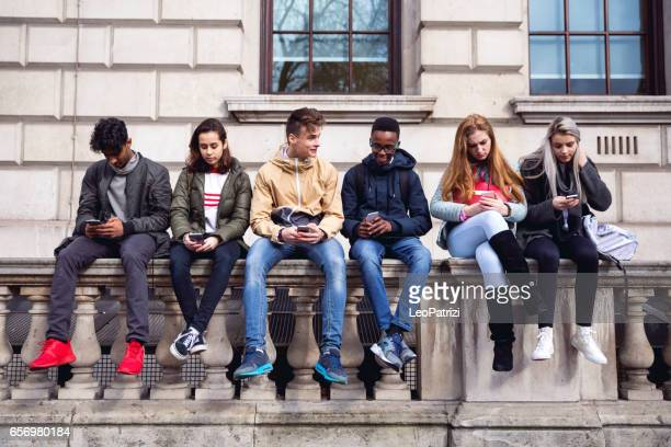 teenagers students using smartphone on a school break - street style stock pictures, royalty-free photos & images