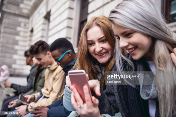 Teenagers students using smartphone on a school break