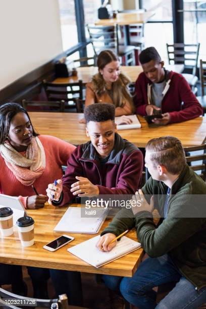 teenagers studying together in coffee shop - teenagers only stock pictures, royalty-free photos & images
