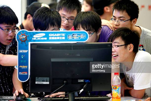 Teenagers surround a computer screen at the ChinaJoy Expo also known as the China Digital Entertainment Expo and Conference in Shanghai China on...