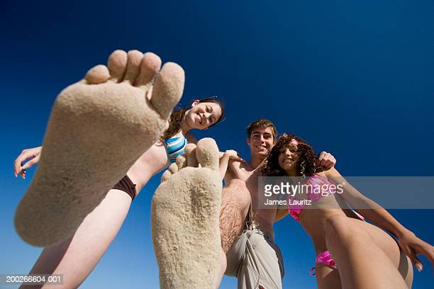 Teenagers (14-17), two holding up sandy feet, portrait, view from below