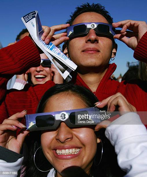 Teenagers use protective glasses to view an annular eclipse at the Planetarium on October 3 2005 in Madrid Spain An annular eclipse is where most of...