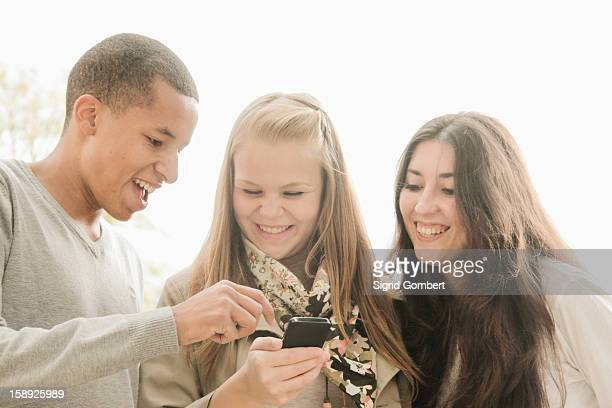 teenagers using cell phone together - sigrid gombert stock pictures, royalty-free photos & images