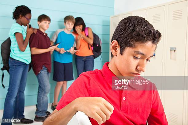 Teenagers using cell phones at school. Cyber bully classmate. Exclusion.