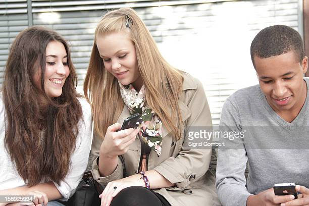 teenagers using cell phones outdoors - sigrid gombert stock pictures, royalty-free photos & images
