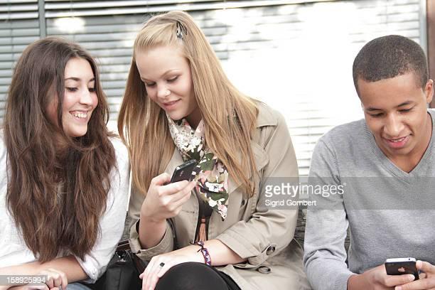 teenagers using cell phones outdoors - sigrid gombert stockfoto's en -beelden