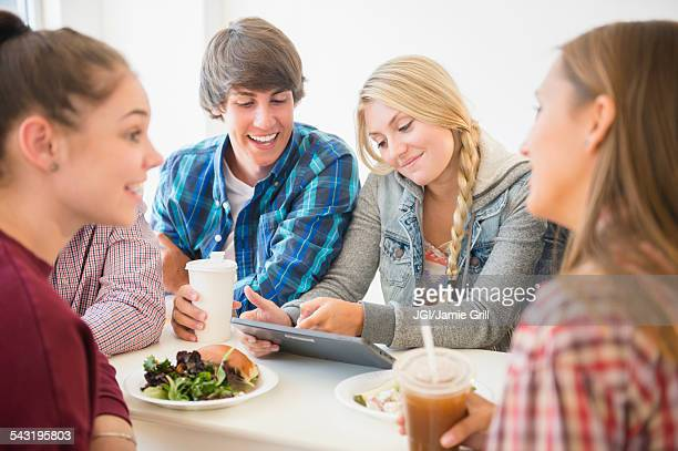 Teenagers using digital tablet at table