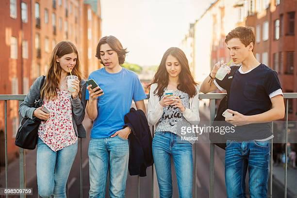 Teenagers using smart phone while drinking juice on bridge in city