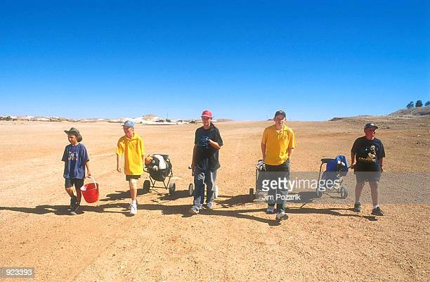 Teenagers walk down the grassless fairways at the Coober Pedy Golf Club January 2000 in the opal mining town of Coober Pedy Australia