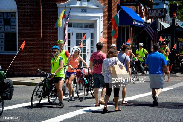 teenagers walking their bikes across an intersection in hyannis, cape cod, massachusetts, usa. - hyannis port stock pictures, royalty-free photos & images