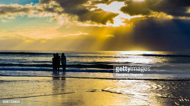 Teenagers watching morning sun rays on the beach of Gold Coast, Australia