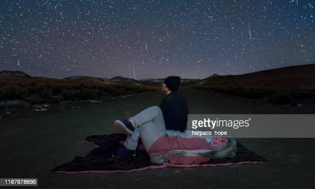 teenagers watching the geminid meteor shower. - geminid meteor shower stock pictures, royalty-free photos & images