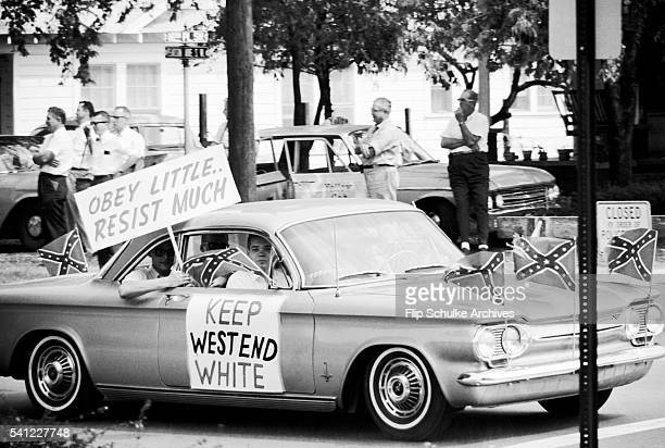 Teenagers wave signs and confederate flags from their car during the fight over desegregating Birmingham's public schools.