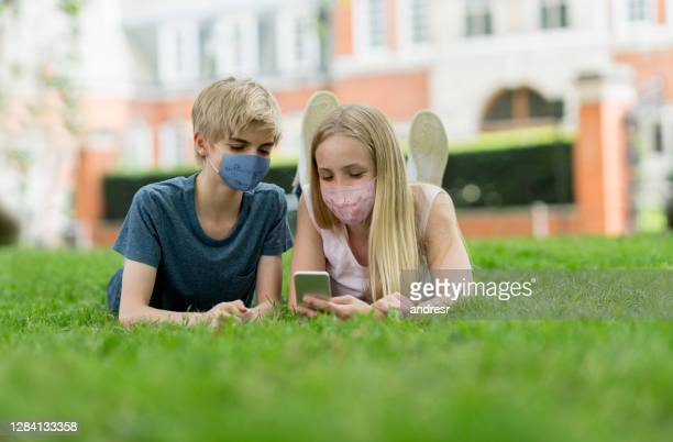 teenagers wearing facemasks while looking at social media at the park - state of emergency stock pictures, royalty-free photos & images