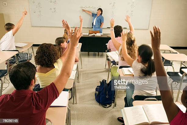 teenagers with arms raised in classroom - thinkstock foto e immagini stock