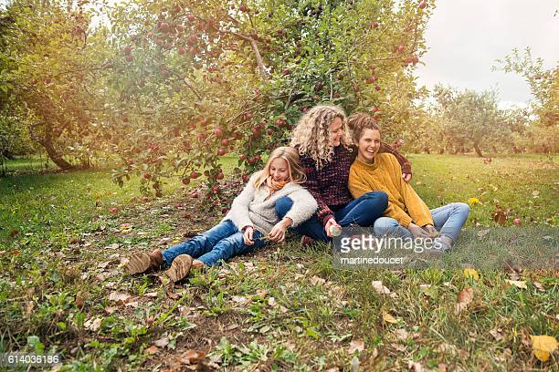 Teenagers with mother enjoying nature in orchard.