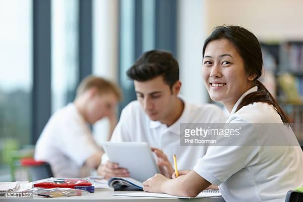 Teenagers working in school classroom