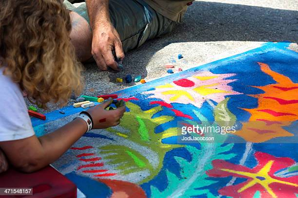 Teenagers working on chalk drawing at street art festival