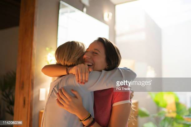teenagr girl and mature woman embracing - arm around stock pictures, royalty-free photos & images