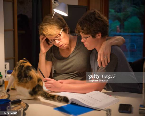 teene boy doing homework with his mother at kitchen counter - home schooling stock pictures, royalty-free photos & images